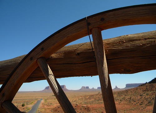 An old wooden wagon wheel decorates a fence in Monument Valley in the American Southwest