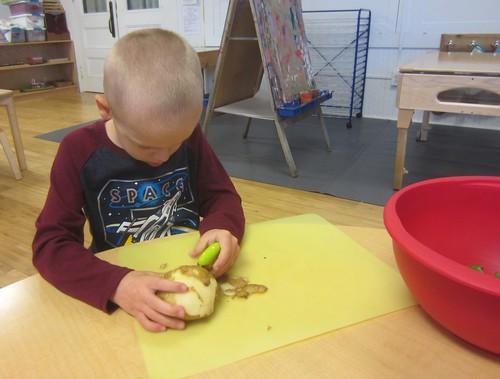 carefully peeling a potato