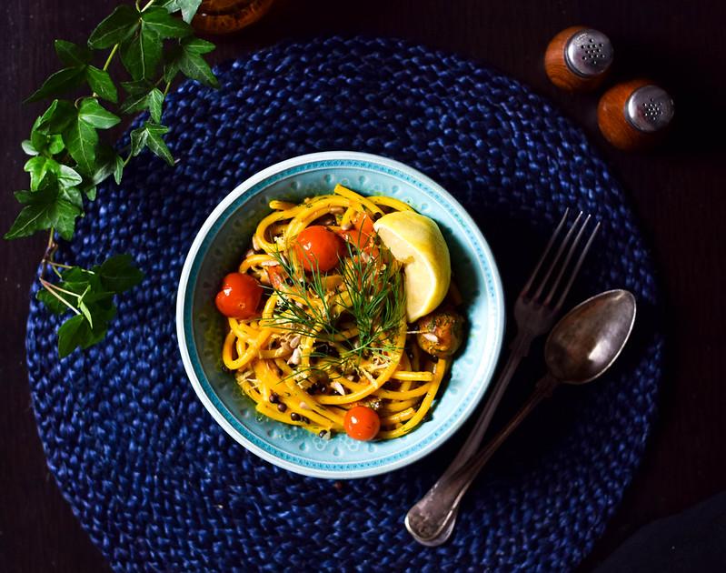 Vegansk tomat- och saffranspasta med dill i en turkos skål på ett mörkblått underlag