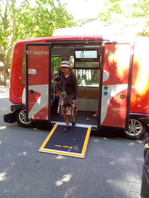 EZ.10 driverless electric shuttle bus from company Easy Mile, on demonstration run in Canberra's city center. Marghanita da Cruz steps out of the bus. The wheelchair ramp has been deployed, as part of a demonstration. This would not normally be used for ambulatory passengers.