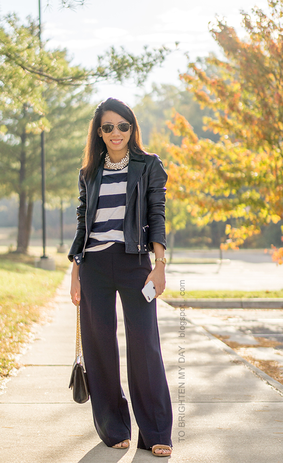 black leather jacket, pearlized necklace, navy and white striped top, gold watch, navy wide legged pants, black shoulder bag, brown suede flats
