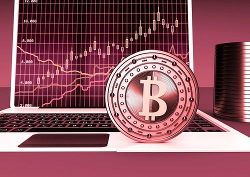 Bitcoin vor Laptop - rot