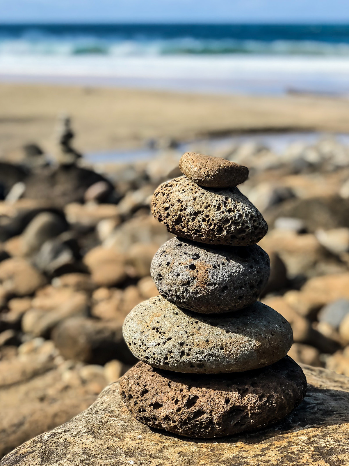 the beach at the end of the trail was covered with dozens of stone cairns