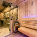 Sauna rated frameless glass pivot door separates sauna and shower