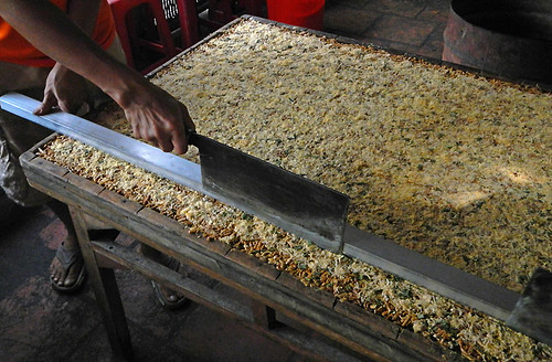 Cutting up a tray of puffed rice sweets in a snack factory on the Mekong River in Vietnam