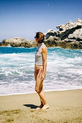 Femme sur une plage aux eaux turquoises