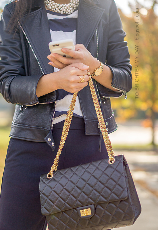 black leather jacket, pearlized necklace, navy and white striped top, gold watch, navy wide legged pants, black shoulder bag
