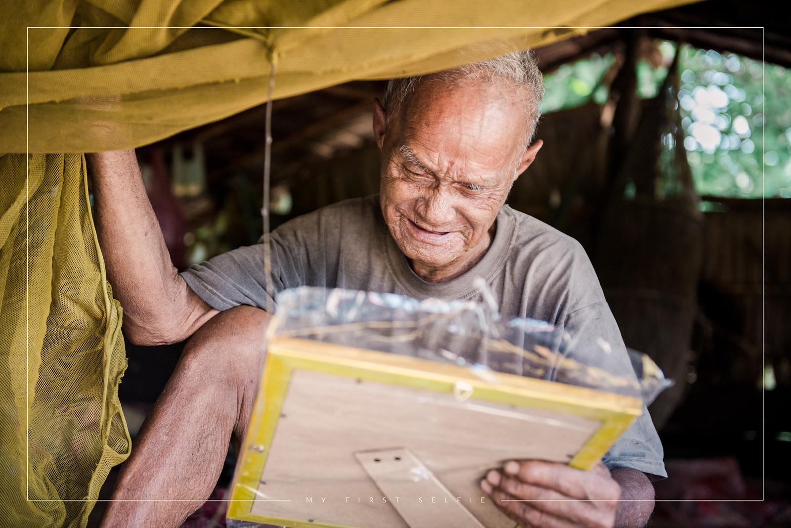 An elderly man enjoying his first portrait photo