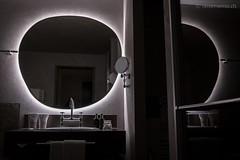 Badezimmer mit unförmigem Spiegel