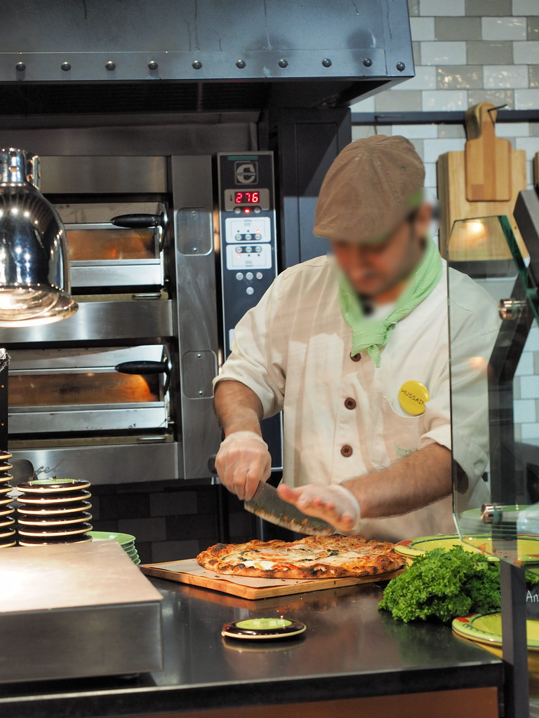 The Italian chef slicing the pizza.