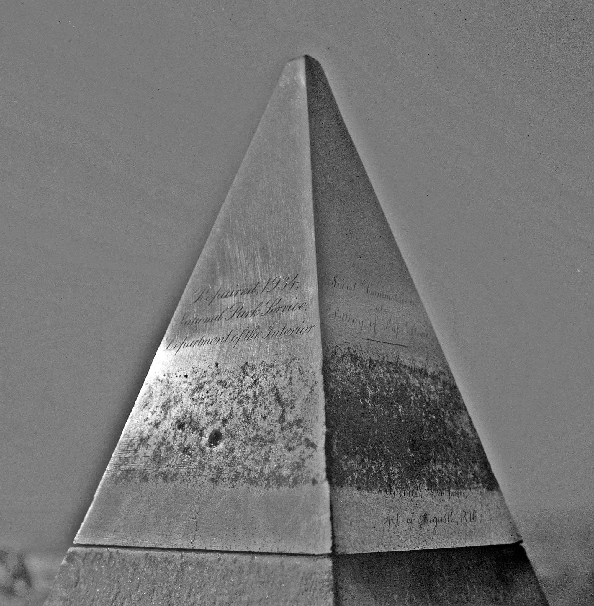 Aluminum apex showing inscriptions on east and north faces. Large dark spot in the center of the mottled area on the east (left) face is a dimple left by one of four set screws that used to hold the copper band to the apex.