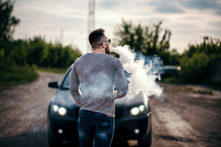 Man Vaping In Front Of Luxury Car
