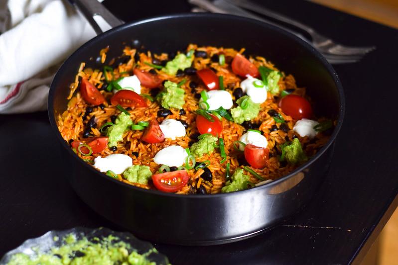 Rött one pan chipotleris med klickar av gräddfil, guacamole och kvartade körsbärstomater