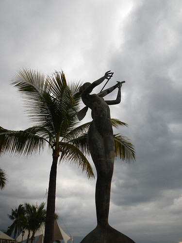 Silhouette of a sculpture of a mermaid with a coconut palm in the background along the Malecon (seawall) in Puerto Vallarta in Mexico