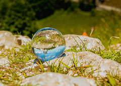 Beautiful blue sky reflected in glass ball