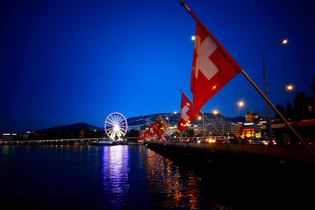 Suisse flag on a bridge in Geneva during night