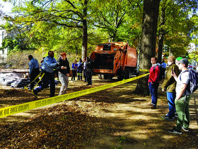 A photo showing several students standing on the outside of a line of police tape while an officer presses a student on the inside of the police tape toward them. Other officers and officials can be seen the background along with a trash truck and a tent.