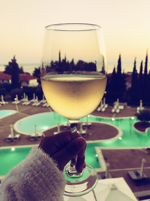 Glass of champagne overlooking a pool at Ikos Olivia at sunset