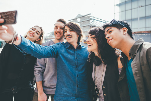 Group of young multiethnic friends taking a selfie with smart phone handhold , having fun - friendship, relaxing concept
