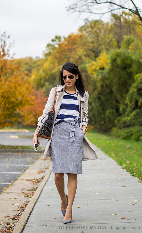 trench coat, navy and white striped top, blue striped pencil skirt with bow, monogrammed tote, oversized watch, gray suede pumps