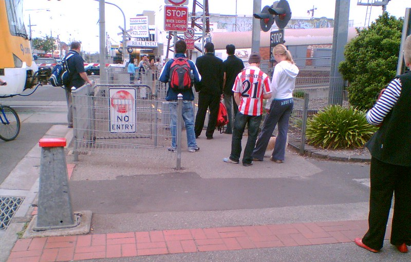 Pedestrians wait at Glenhuntly level crossing