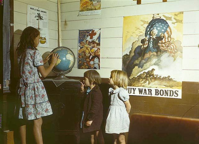 Rural school children in front of World War II homefront posters. One studies a globe atop a Victrola. Photograph taken by John Vachon in San Augustine County, Texas, April 1943.