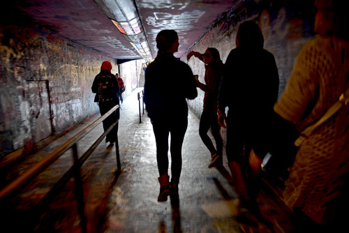 A high school student and her family get a tour of the Free Expression Tunnel by an NC State upperclassman.