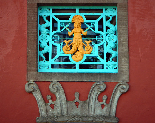 Window grating featuring a fanciful two-tailed Mermaid in the village of Portmeirion, Wales
