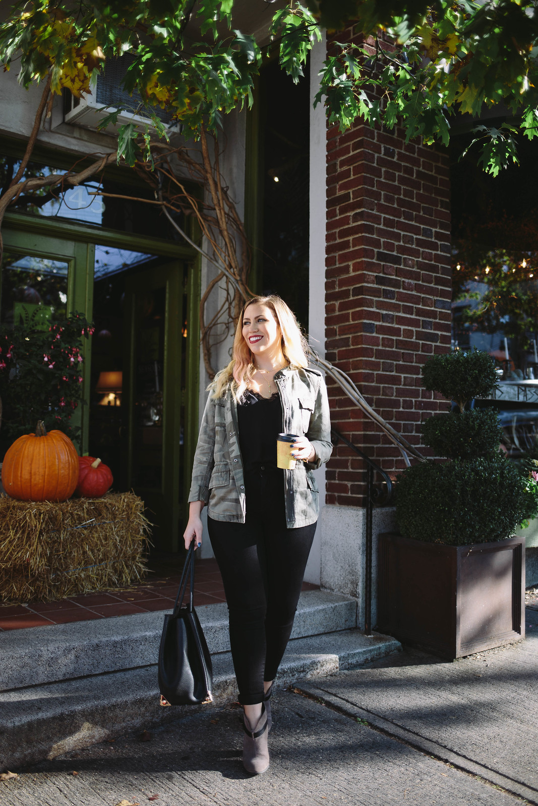 Casual Fall Outfit Camo Jacket Black Jeans Booties Coffee Shop Pumpkins Haystack
