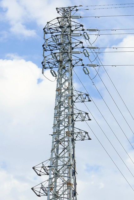 Okegawa_Transmission Tower_(2017_12_05)_1_resized_1 高圧送電線の鉄塔の写真。 雲のある空を背景に鉄骨の塔が立つ。 送電線が幾本も伸びている。