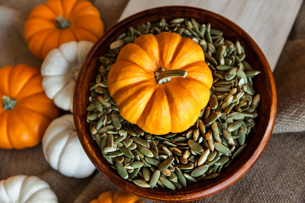 Closeup of Full Bowl of Peeled Pumpkin Seeds with Orange Pumpkin, Autumn Holidays