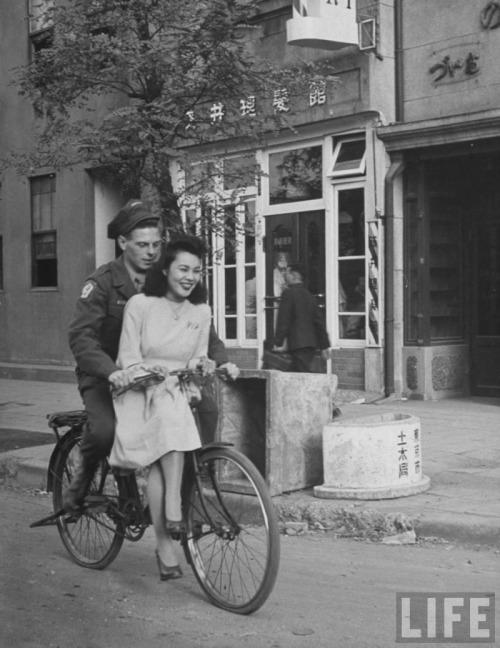US soldier giving Japanese girl a bicycle ride, with handlebar riding forbidden. Japan, 1946