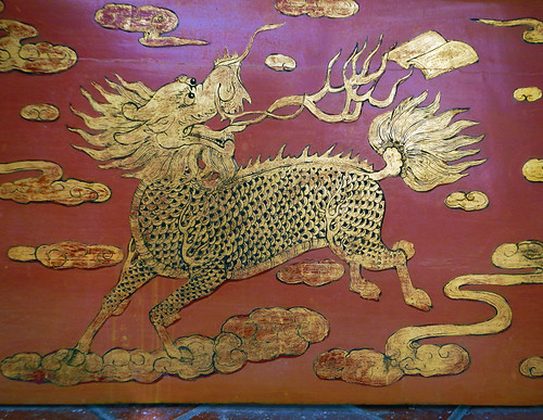 Red & gold painting of a mythical creature combining a lion with the hoofs of a deer in a Melaka Temple in Malaysia
