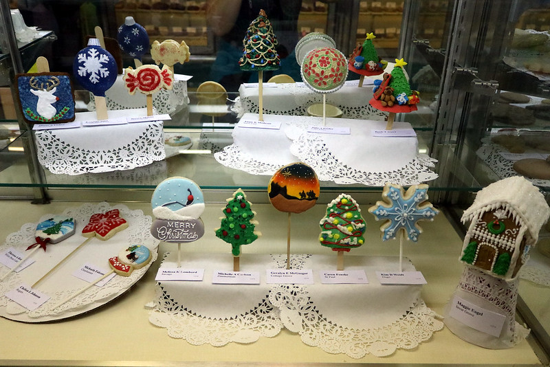 a display of 14 cookies on sticks, such as a reindeer portrait, a white star on a red background, four decorated trees, and a winter version of the Spoonbridge and Cherry