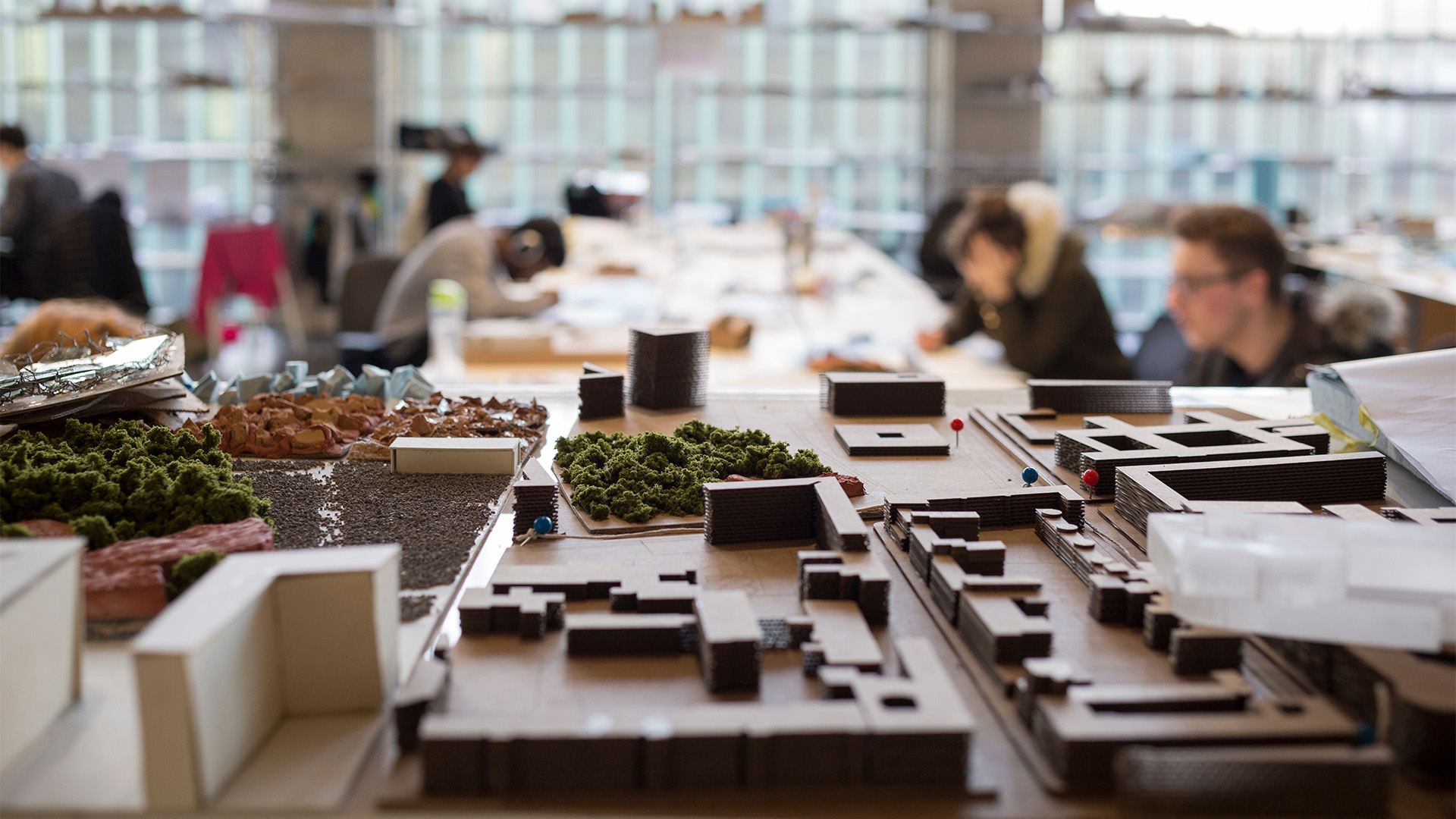 Close up of architectural model with students working in studio in background