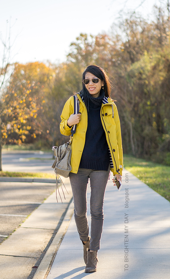 yellow rain jacket, navy turtleneck sweater tunic, gray skinny jeans, gray tote with stripe strap, gray suede ankle boots with fringe
