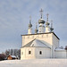 The White Sts. Peter and Paul Church on a Small Hill Covered Snow