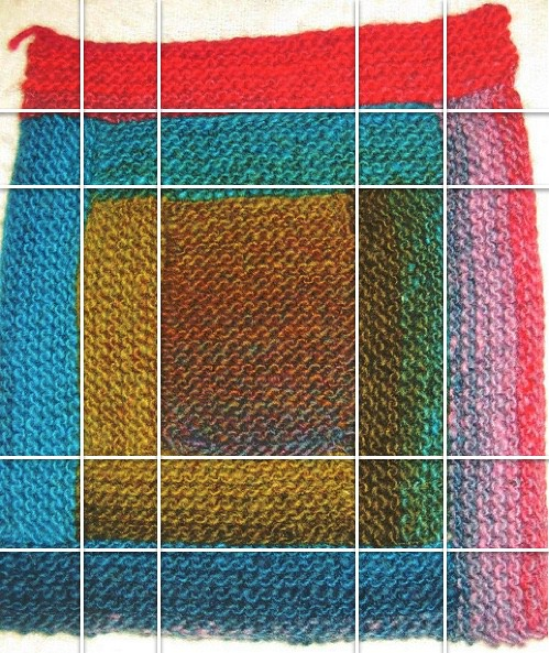 Knit log cabin blanket square with lines demarcating the columns and rows.