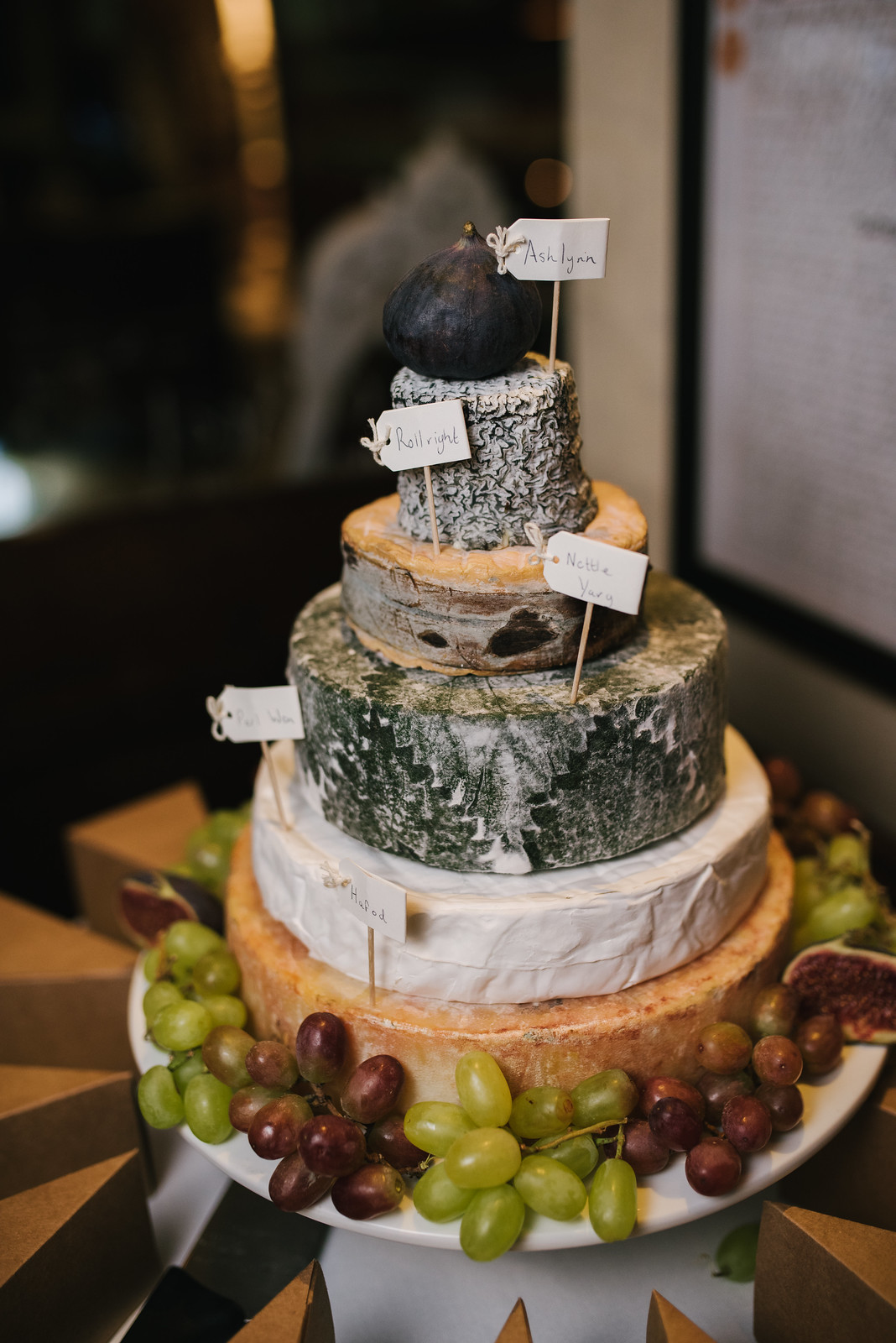 a picture of a cheese tower dressed with figs and grapes