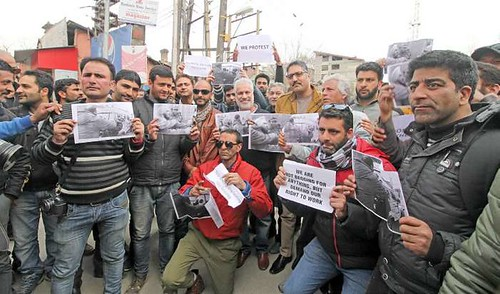 Journalists-display-pictures-showing-the-police-officer-attacking-Tauseef-Mustafa