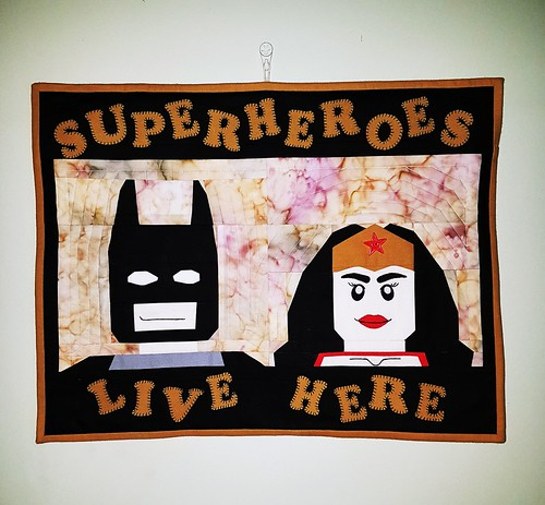 Lego Batman and Wonderwoman blocks made into a wallhanging. Patterns on fandominstitches.com Pieced by Hannah Hughes