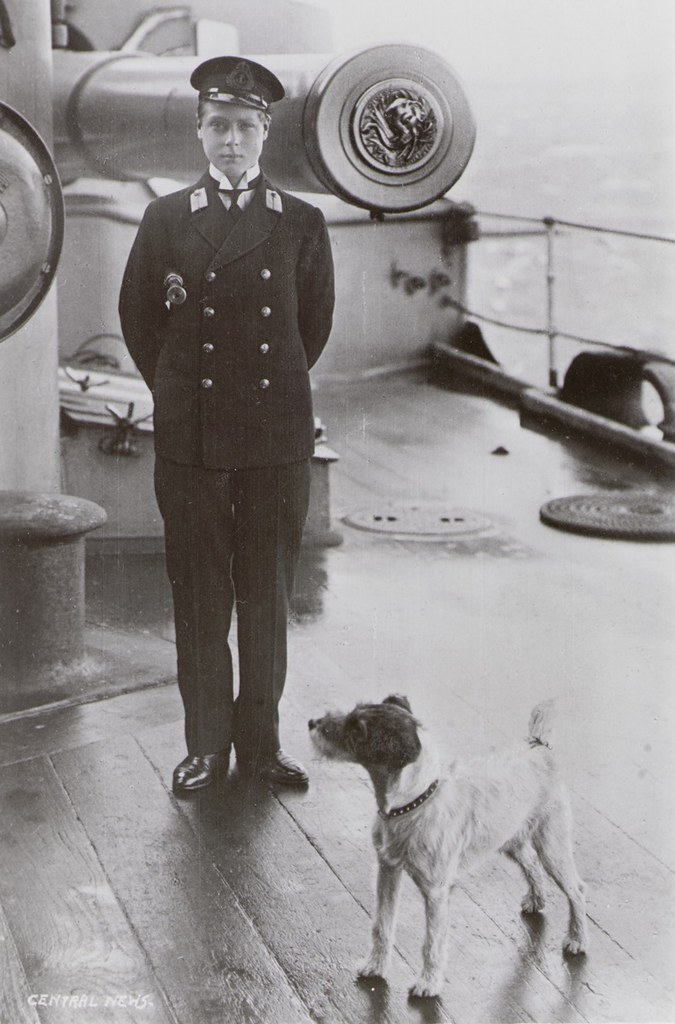 Photograph of HRH Edward Prince of Wales, standing with a terrier in front of a 9.2 inch gun on board HMS Hindustan, 1910