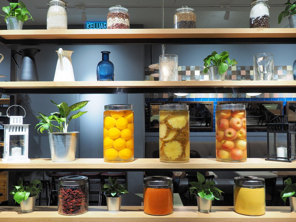 Big shelf in Marché Mövenpick Pavilion filled with pots, fruits in jars and plants