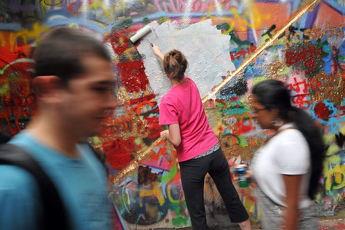 Walkers pass by a student as she whitewashes the Free Expression Tunnel in preparation for Respect The Pack.
