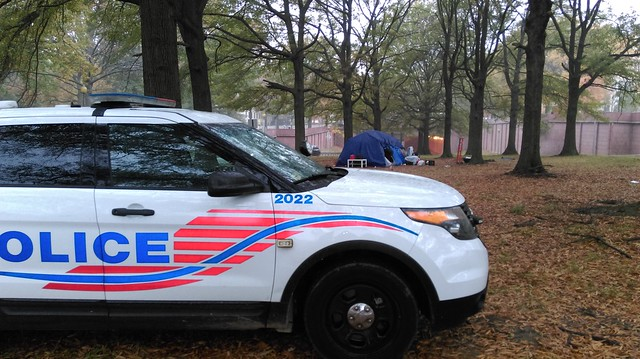 Photo of an MPD SUV parked in the grass in front of a tent.