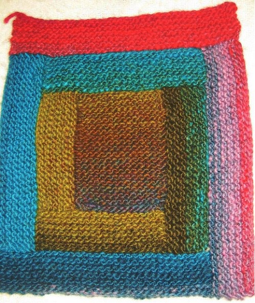 Knit log cabin blanket square, showing color gradiation from the center outward in a counter-clockwise direction