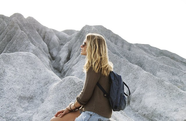 A girl sits on a rock during the gap year