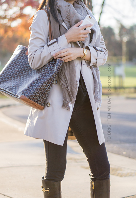 trench coat, plaid scarf, black twist front top, brown belt, gold watch, black jeans, black riding boots, monogrammed tote
