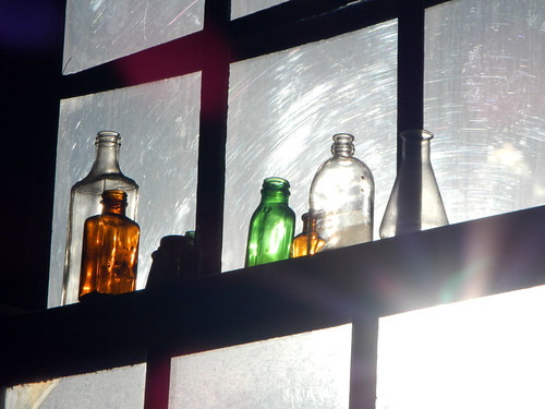 A window with bottles at 1000 Parker St in Vancouver, Canada