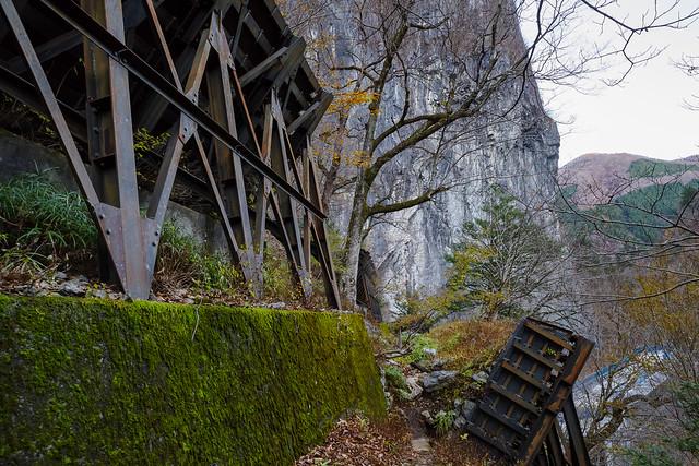落石防止の頑丈なフェンスの間から山道へ取り付く